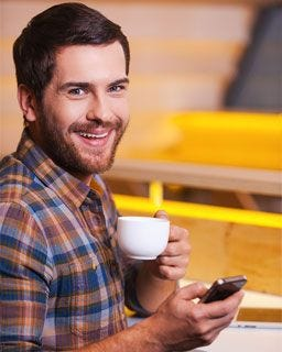 Guy enjoying a cup of coffee while using his phone